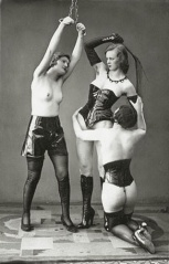 Female whipping woman while another watches.jpg