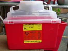 A large sharps container. Note the biohazard symbol. These containers are designed with an opening on top through which used needles can be dropped. However, once inside the needles can't fall back out, even if the container is tipped upside down. The container is also very tough and difficult to open