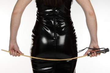 Rear view of female model in black dominatrix outfit holding a cane.jpg